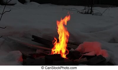 Real flames in the fire with burning logs and snow around.