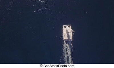 Aerial top view of sailing white yacht in empty ocean blue...
