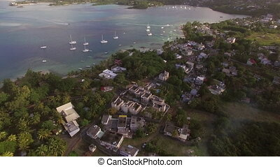 Mauritius Island and yachts in the bay, aerial view - Flying...