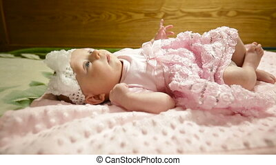 little baby girl in a pink dress lies on a bed.
