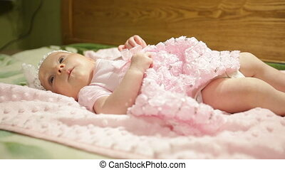 little baby girl in a pink dress lies on a bed