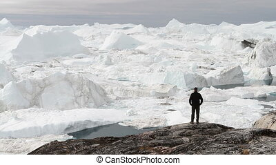Tourist walking in front of glacier - A tourist looks at a a...