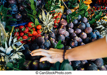 Cropped image of a customer choosing juicy fresh ripe fruit...