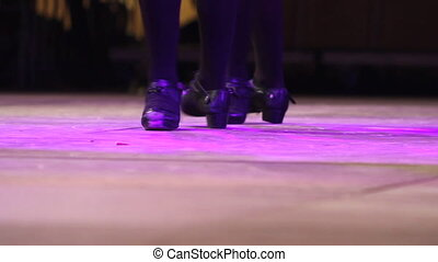 Female feet dancing Irish dance on stage with traditional...