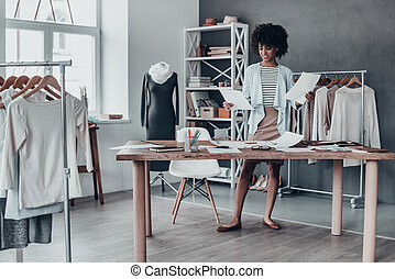 What design is better? Full length of young African woman looking at papers and smiling while standing in her studio near the clothes hanging on the racks