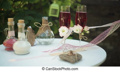 two glasses with champagne and wedding attributes to the...