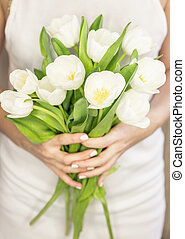 Young woman holding a bouquet of white tulips. Wedding...