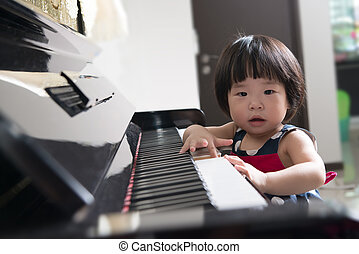 Little Asian child at piano