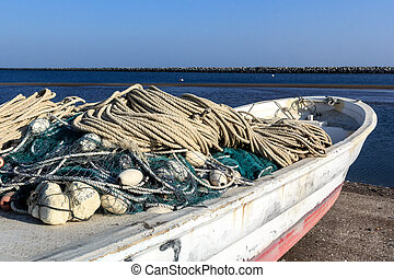 fishing nets by boat before going out to sea