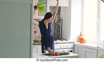 Slow motion of funny woman cook dance with green lettuce while cooking in kitchen at home