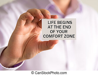 Businessman holding a card with LIFE BEGINS AT THE END OF...