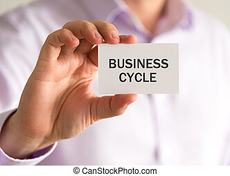 Businessman holding a card with BUSINESS CYCLE message -...