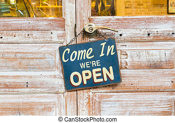 Come In We're Open on the wooden door. center of the photo.