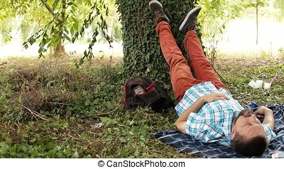 Sleeping Man Leaning Feet Against Tree