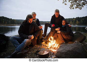 Young Friends With Coffee Cups Sitting Near Campfire -...
