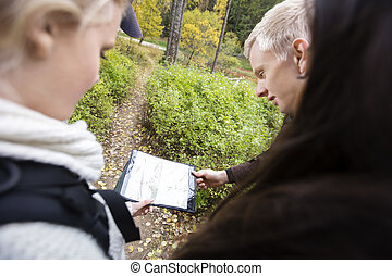 Friends Holding Map While Hiking In Forest