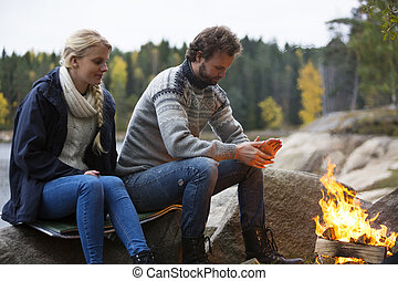 Couple Warming Themselves By Bonfire - Young couple warming...