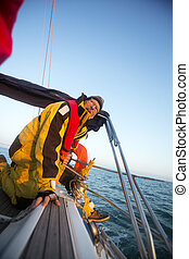 Man Cranking A Winch On Yacht In Sea - Mature man cranking a...