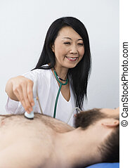 Happy Doctor Performing Ultrasound Treatment On Patient -...