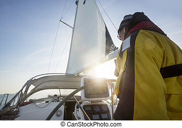 Mature Man At Helm Sailing Yacht - Low angle view of mature...