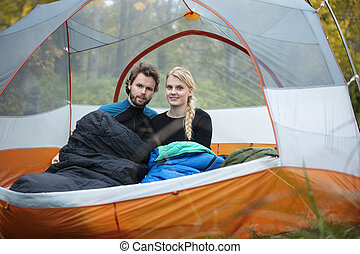 Young Couple With Sleeping Bags In Tent - Portrait of young...