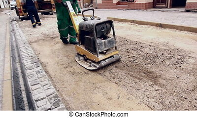 Vibrating machine is compacting soil at the construction...