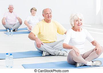 Yoga class for seniors - Group of seniors attending yoga...
