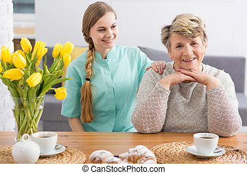 Caregiver spending time with old woman - Young smiling...