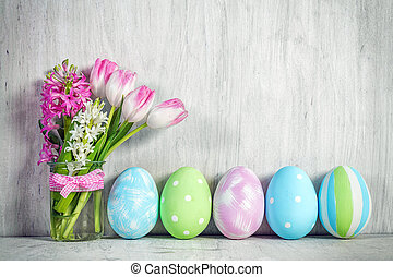 Easter eggs and a spring bouquet of tulips on a wooden...