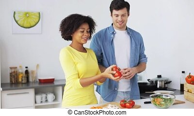 couple cooking food and juggling tomatoes at home - people,...