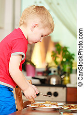 Little boy preparing pancakes for breaktfast
