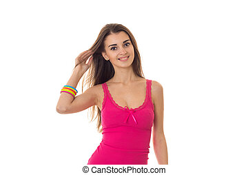 beautiful young girl in pink t-shirt looks into the camera, smiles and keeps hand hair