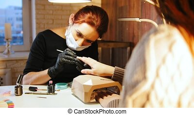 Labour of manicurist - nail master in medical mask doing professional manicure