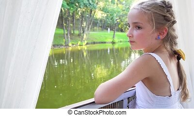 young cute girl looking through window during boat trip on...