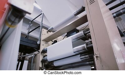 Paper in the process of a printing machine work. Printing establishment detail on production line with sound.