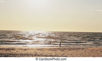 A young girl in a white dress is walking on a sun-lit sandy...