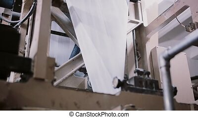 Paper in a printing machine. Printing establishment detail on production line with sound.