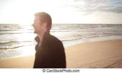 A young dark-haired man in a black coat is walking along the sea shore enjoying the sun rays.