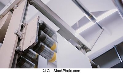 Process of printing at a printing establishment. Paper in a printing detail on production line with sound.