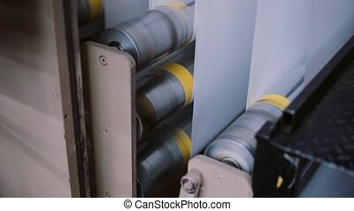 Paper in a printing machine at a printing establishment. Printing detail on production line with sound.
