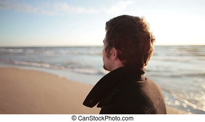 A side view of a young dark-haired man in a black coat is walking along the sea shore.