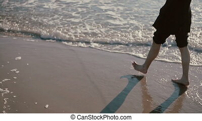 A young man is walking on a beautiful beach with his jeans rolled up and soaking his feet in the sea.