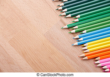 Row of colorful pencils on wooden background - Row of...