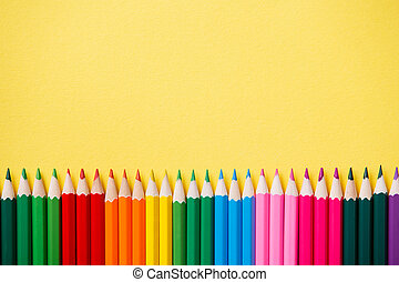 Row of colorful pencils on yellow background. Vertikal...