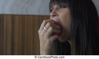 Pretty brunette young woman eating apple