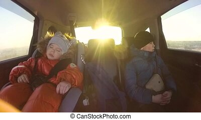 Children riding in the car. The sun's rays through the glass. Slow motion