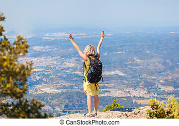 Female traveler with a backpack on her back enjoying the...