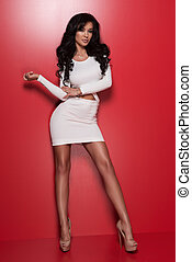Beautiful model in white dress posing on red background