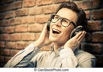 positive music - Happy young man listens to music in...