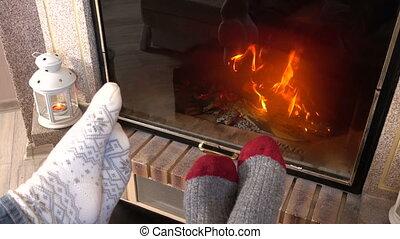 wiggling legs in woolen socks heat up near fireplace -...